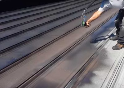 Roofers Spray Painting Metal Roof in Orlando FL
